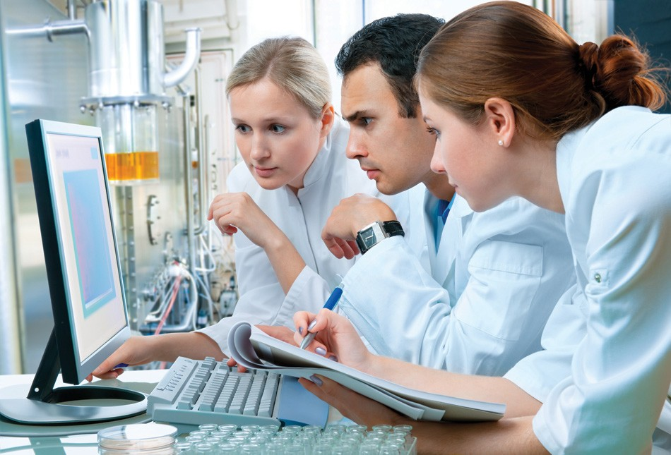 researchers in lab coats in front of a computer